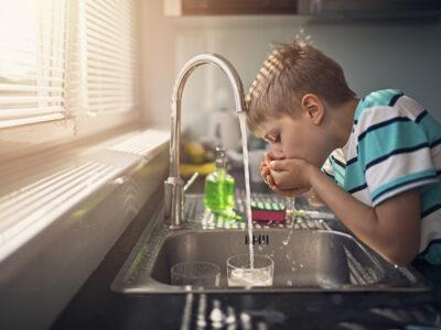 Little boy drinking tap water